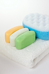 Three soap bars of same size but different colors (orange, white and green) and textures, on a white fluffy towel folded in half and next to a double sided blue and white porous sponge. The bars have a slightly concave shape with curved corners.