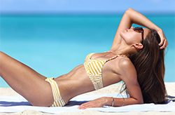 53759159 - sexy suntan beach woman sunbathing in fashion bikini. beautiful fit body of model relaxing tanning on towel. weight loss or skin care sun protection concept.